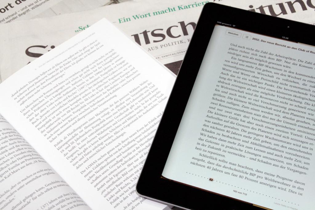 Ökobilanz E-book Reader und Printmedien nebeneinander auf dem Tisch