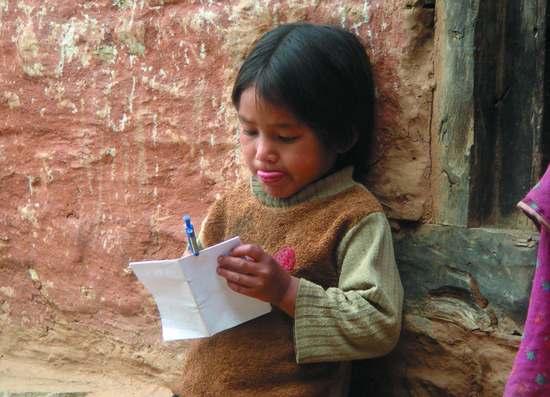 Mädchen aus Nepal hält Papier und Stift in der Hand